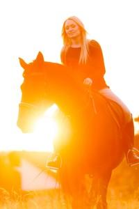 Junge hübsche Frau genießt Ihre Freizeit an einem wunderschönen Sommerabend mit Ihrem Pferd.