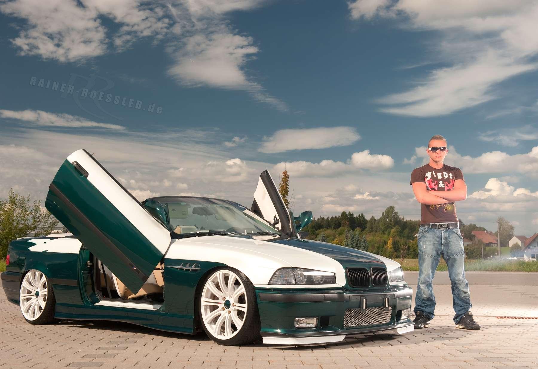 Hübscher Mann steht neben seinem edel-getunten BMW Automobil. Beim Fotoshooting mit Fotograf Rainer Rössler