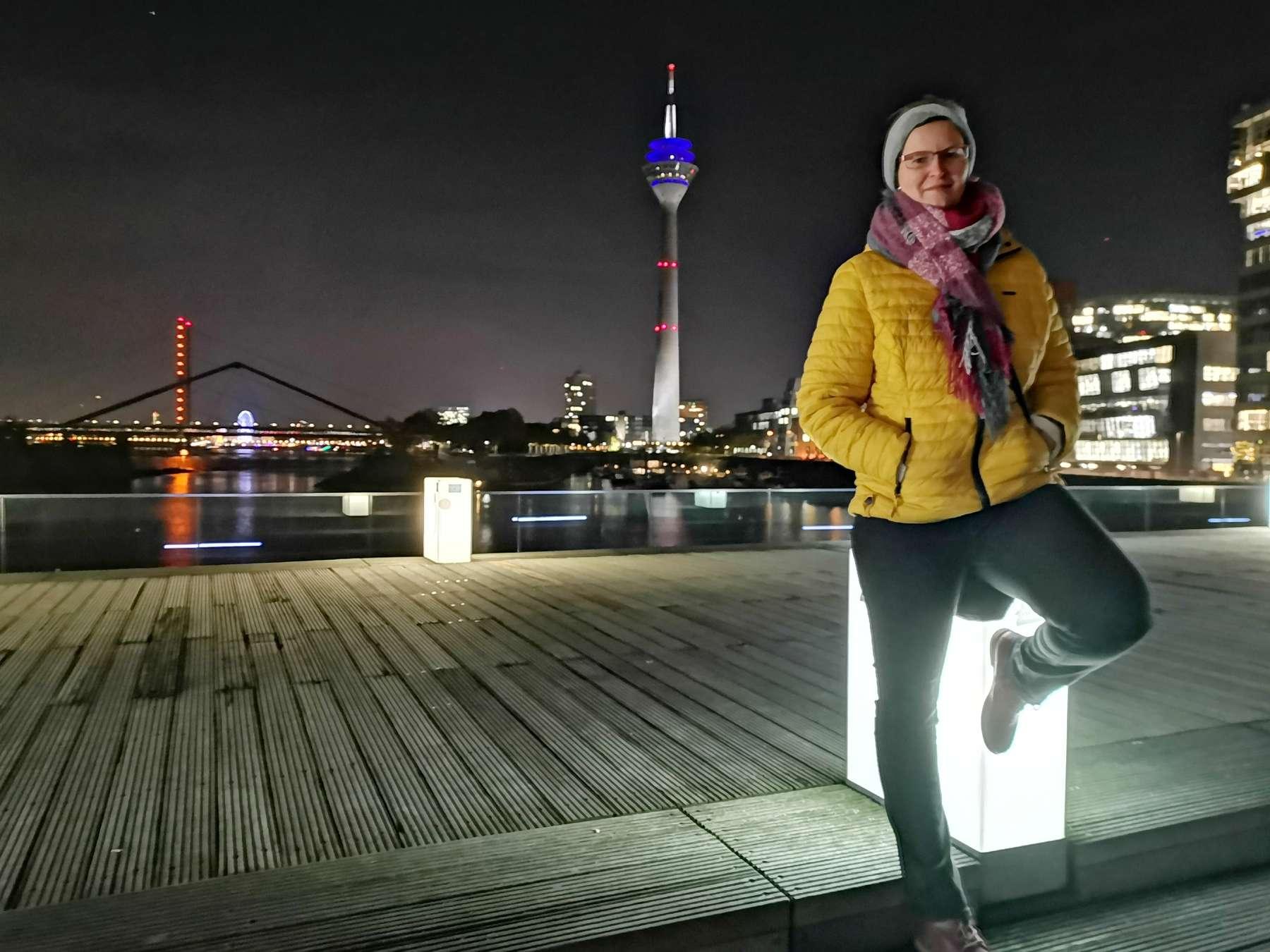 Hübsche Frau bei einem Fotoshooting mit Fotograf Rainer Rössler im abendlichen Düsseldorf auf der Brücke im Medienhafen. Im Hintergrund sind die Lichter der Stadt zu sehen.