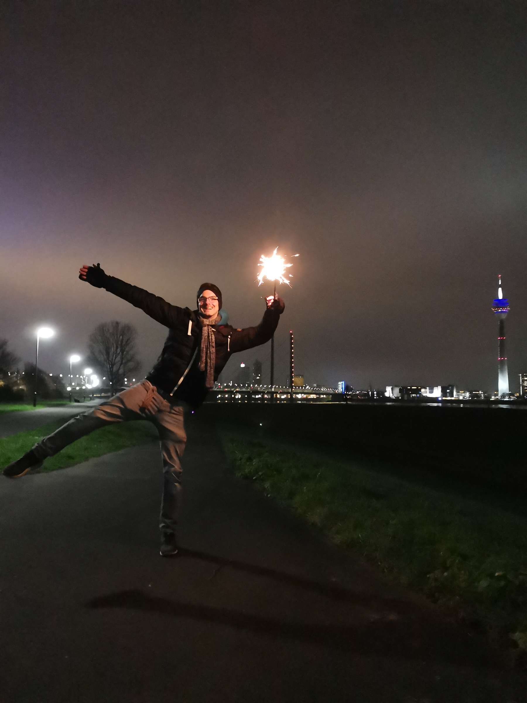 Hübscher Mann auf einem Bein balancierend am Silvesterabend mit einer Wunderkerze am Rheinufer Düsseldorf fotografiert.