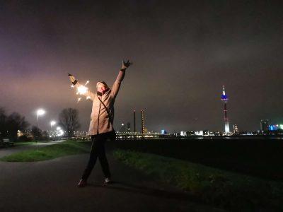 Hübsche Frau mit Wunderkerze in einem grauen Mantel posiert für den Fotografen am Silvester Abend vor der Skyline von Düsseldorf.