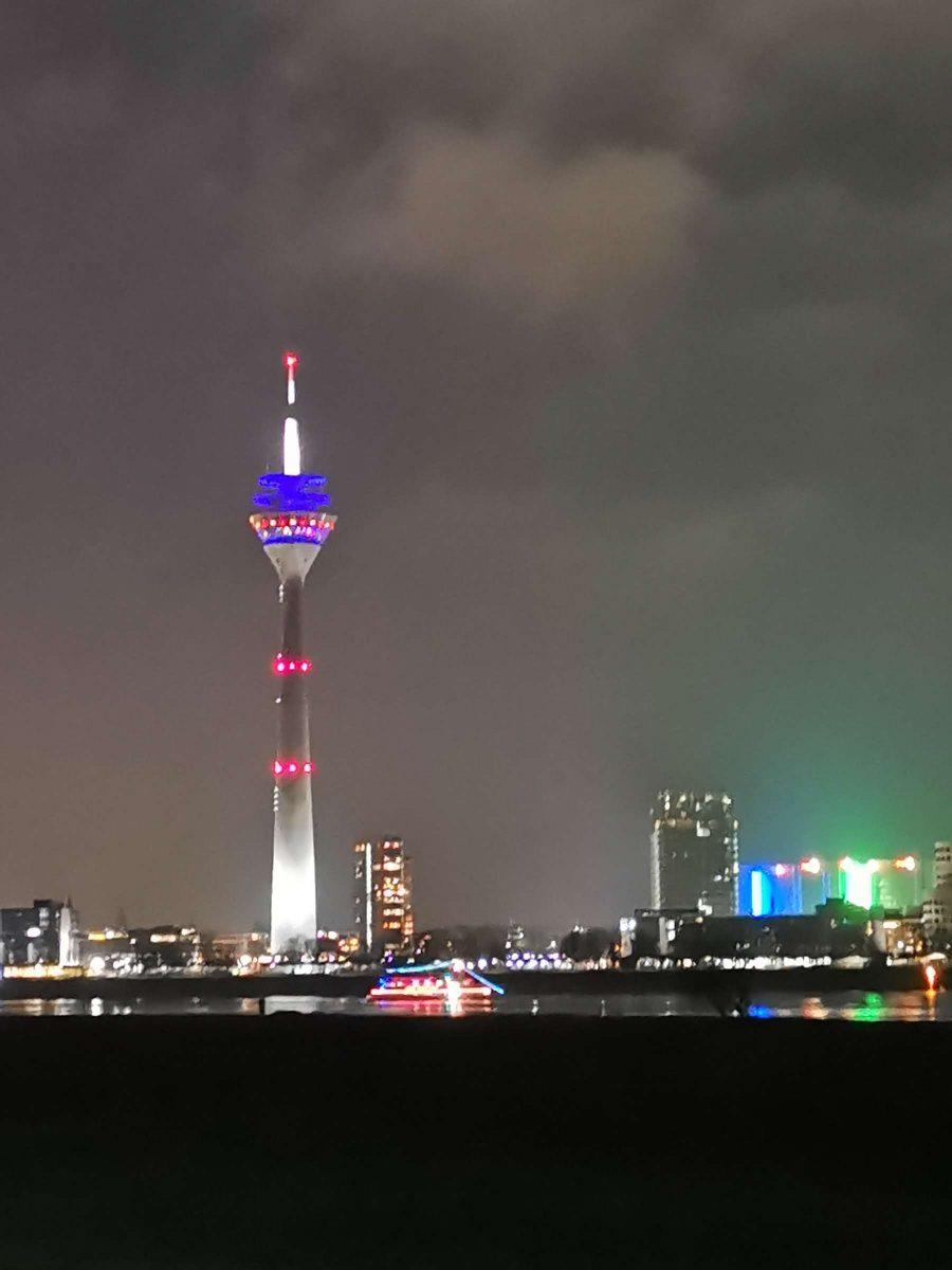 Partyboot mit Ambiente Lichtern vor dem beleuchtenden Rheinturm Düsseldorf fotografier von Fotograf Rainer Rössler mit einem Huawei Mate 20 Pro