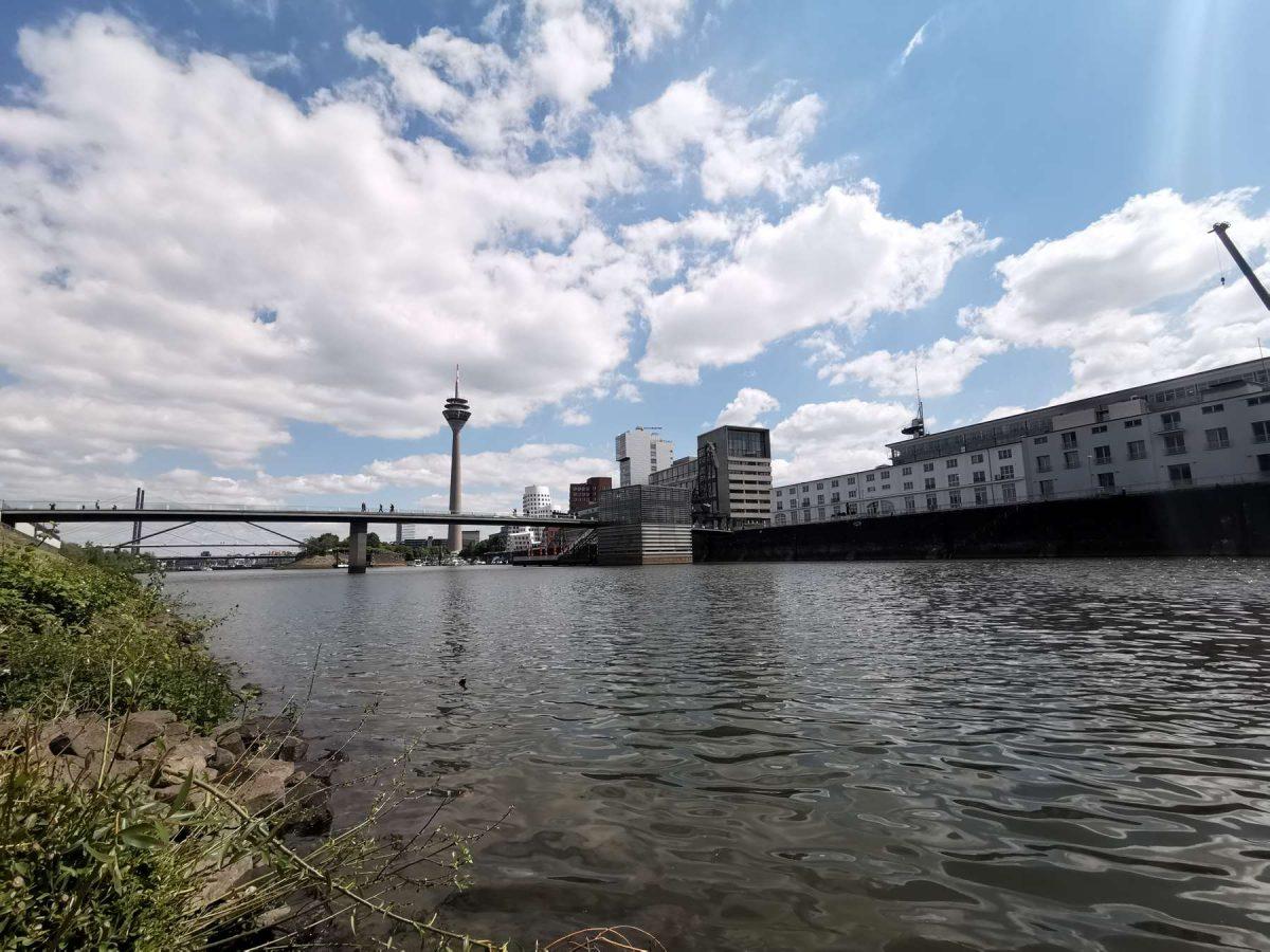 Wie Yin und Yan - der fließende Rhein schlängelt sich durch die massiven, designstarken Bauten im Medienhafen Düsseldorf