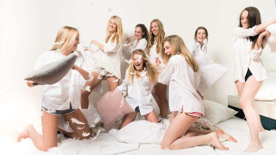 Personenfotograf zuhause - Freundinnen haben Spaß bei einer Kissenschlacht im Rahmen eines Fotoshootings zuhause im eigenen Bett
