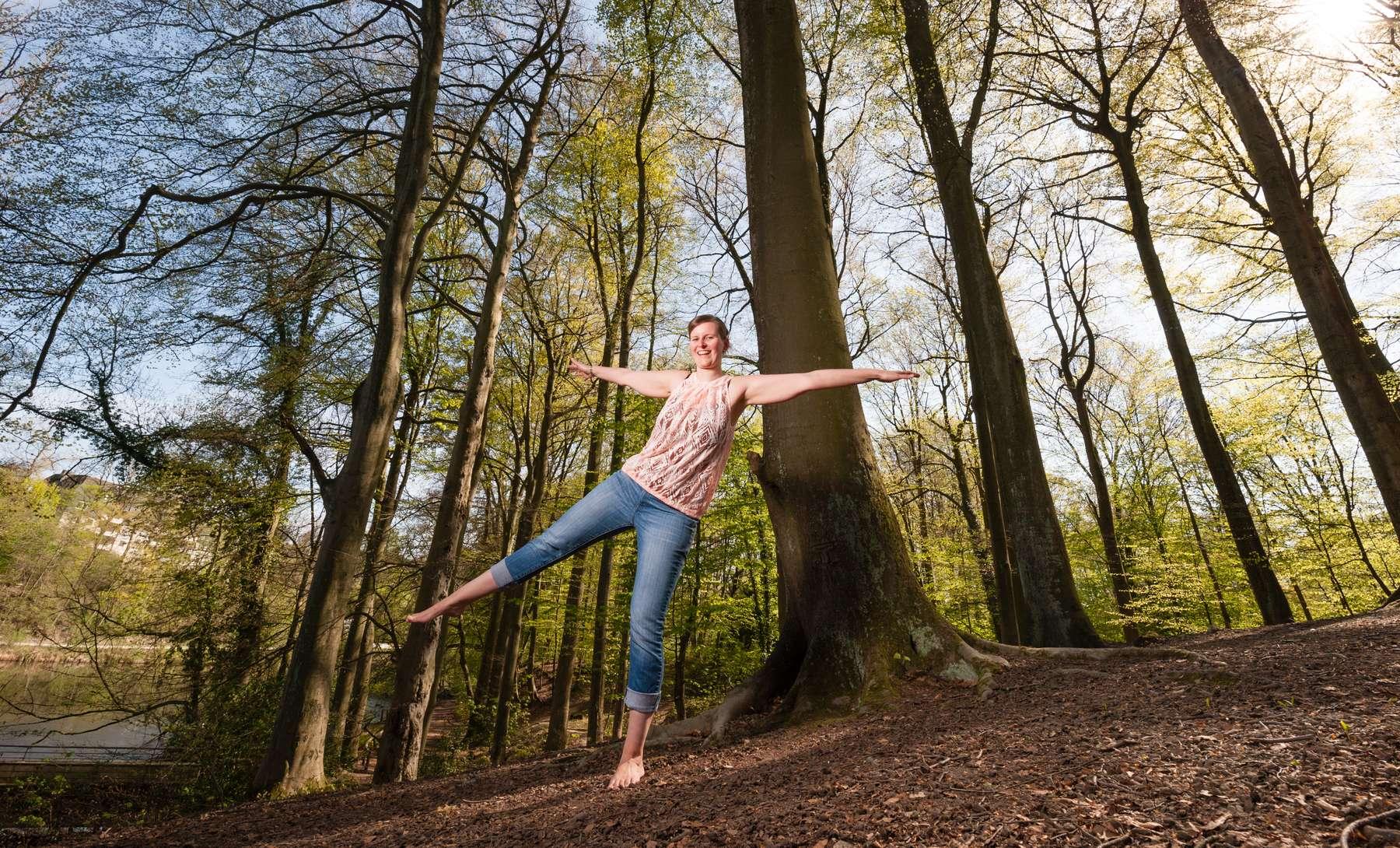 Personenfotograf Essen - Dynamisches Frühlings-Fotoshooting mit Barfuß-Balance-Übung einer jungen Frau im grünen Stadtwald der Margarethenhöhe inmitten der Stadt Essen