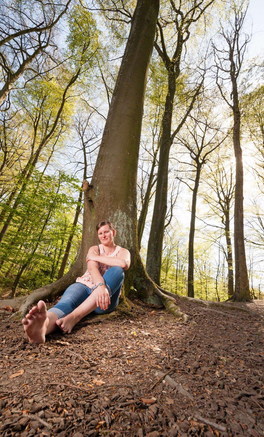 Personenfotograf Essen - naturverbundene junge Frau posiert barfuß umgeben von Bäumen bei einem Frühlings-Fotoshooting in der Margarethenhöhe inmitten der Stadt Essen