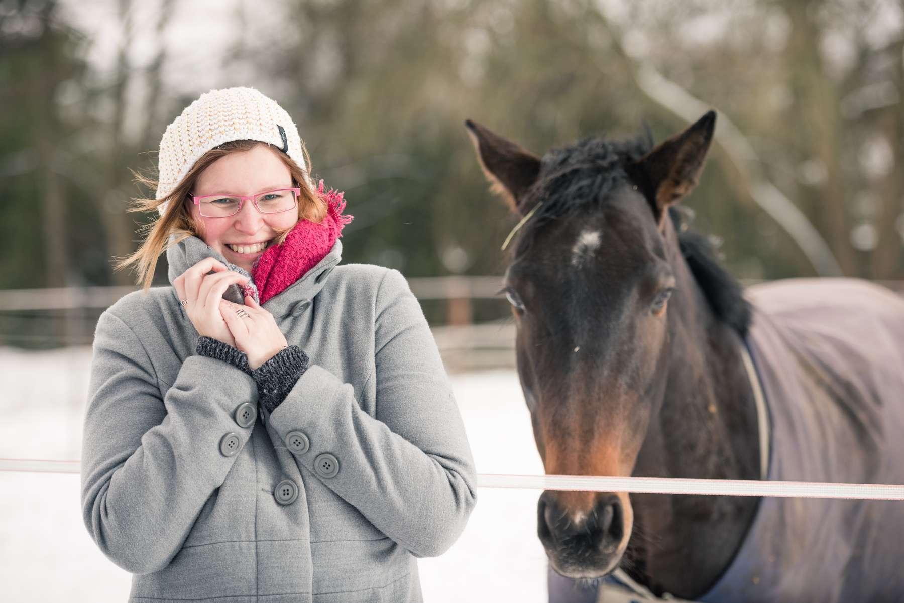 Junge hübsche Frau lächelt trotz Kälte am verschneiten Tag mit Ihrem Pferd um die Wette