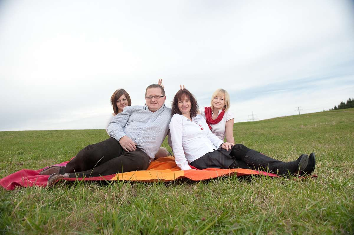 Familienfoto einer glücklichen Familie beim Fotoshooting mit einem Fotograf draussen auf einer Wiese