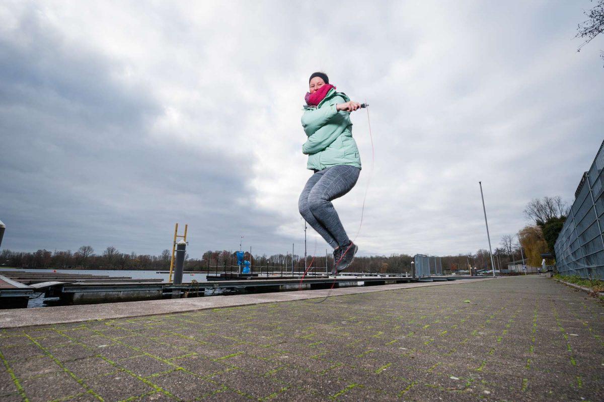 Lifestyle-Fotoshooting am Unterbachersee bei Düsseldorf mit einer jungen hübschen Frau beim Seilspringen