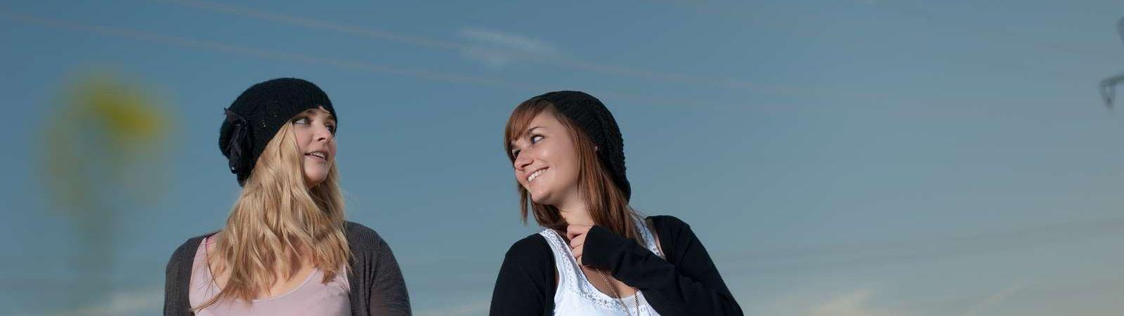 Zwei Freundinnen beim Fotoshooting in einer sommerlichen Wiese geniessen ihre Aufnahmen für Fotos für die Ewigkeit