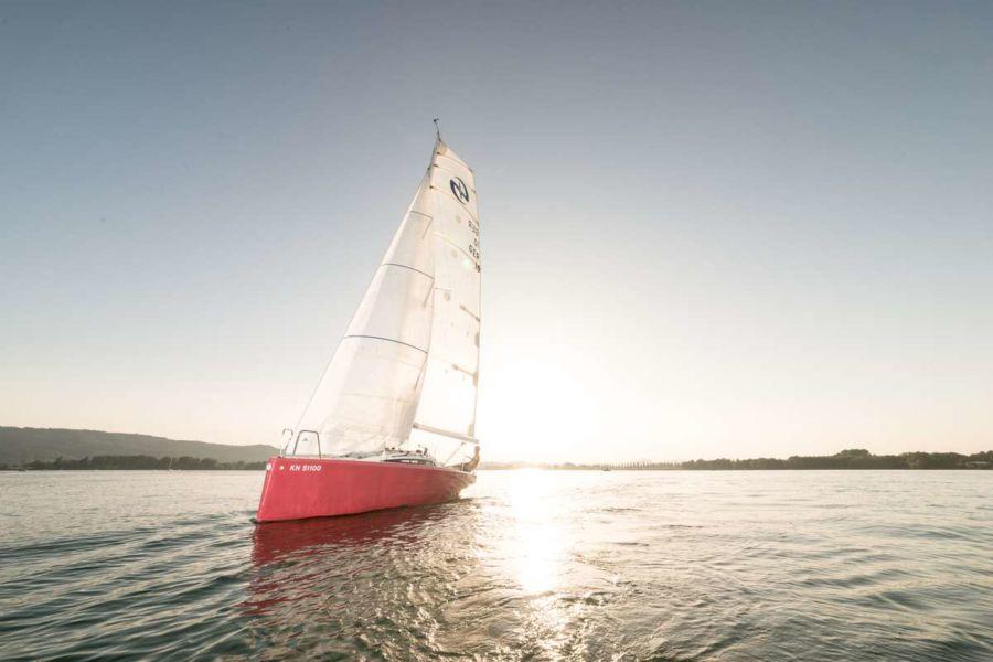 Rotes Segelschiff RedSaphira fotografiert vor der Abendkullise von Radolfzell am Bodensee von Fotograf Rainer Rössler.