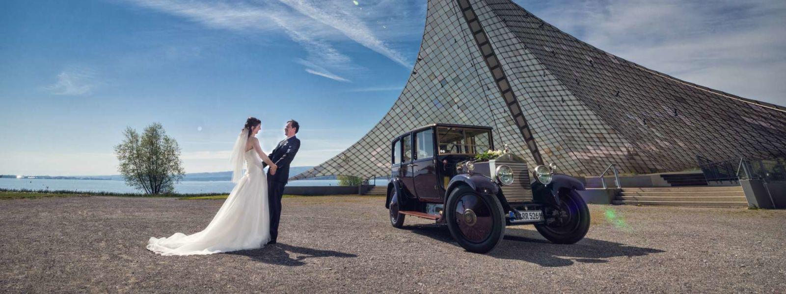 Brautpaar beim Fotoshooting mit Hochzeits-Oldtimer am Konzertsegel an ihrem Hochzeitstag in Radolfzell