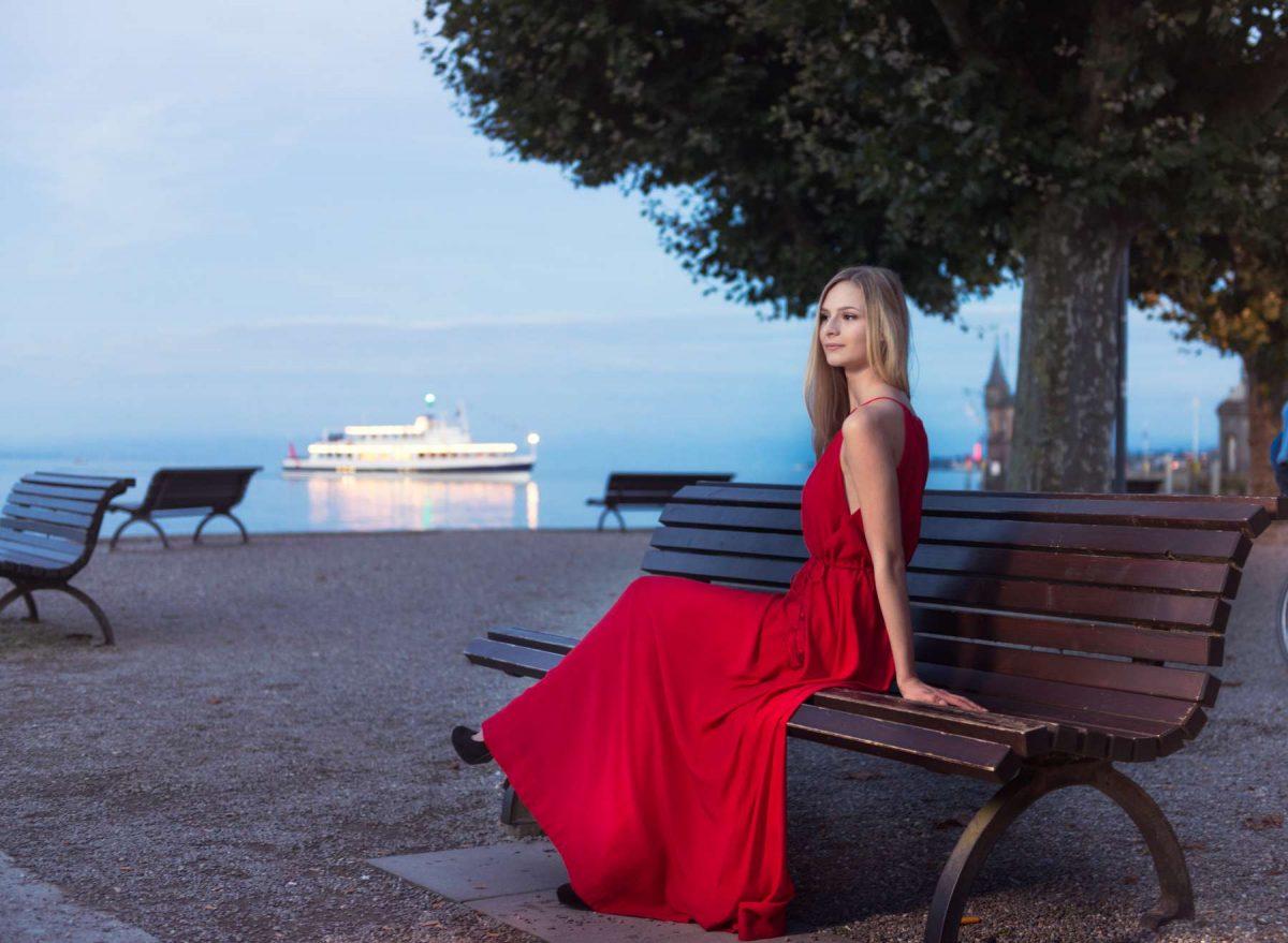 Model Jenny H. in einem eleganten roten Abendkleid abgelichtet abends zur blauen Stunde von Fotograf Rainer Rössler bei der Promenade in Konstanz am Bodensee