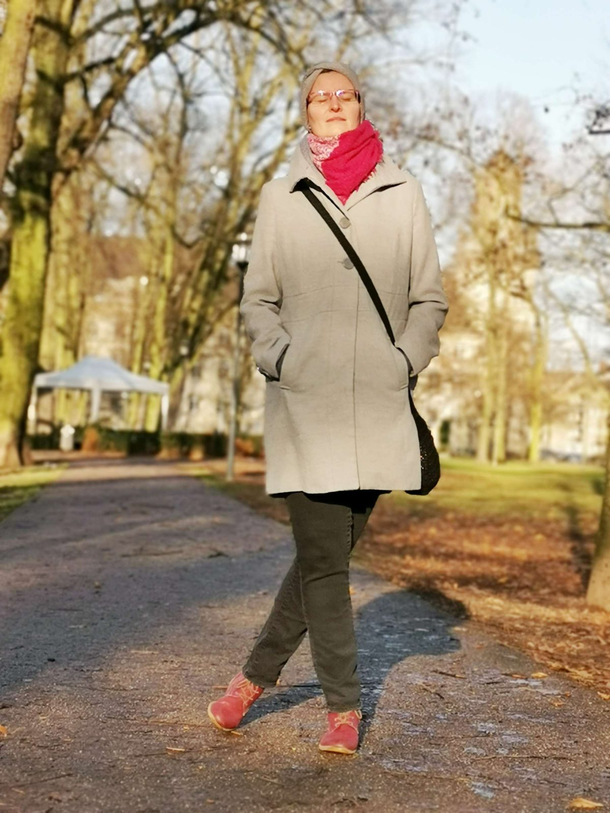 Hübsche Frau steht an einem sonnigen Wintertag im Dezember 2019 im Krefelder Stadtgarten und lässt sich von Fotografen Rainer Rössler mit seinem Smartphone ablichten.