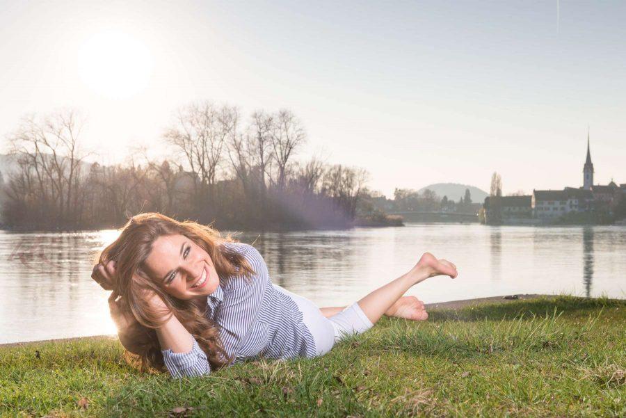 Hübsche Frau liegt am Rhein in Stein am Rhein (Schweiz) auf einer Wiese und genießt das Fotoshooting mit Fotograf Rainer Rössler